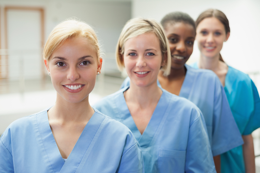 Millennial nurses stand in a line and smile.